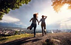 Amici che corrono al paesaggio urbano nelle montagne Fotografie Stock Libere da Diritti