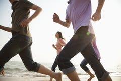 Amici che corrono alla spiaggia Fotografia Stock