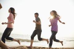 Amici che corrono alla spiaggia ed a divertiresi Immagine Stock