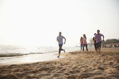 Amici che corrono alla spiaggia ed a divertiresi Fotografie Stock