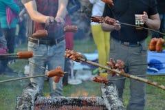 Amici che cucinano la salsiccia del hot dog Immagini Stock