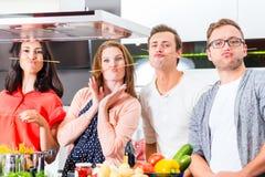 Amici che cucinano pasta e carne in cucina domestica Immagine Stock