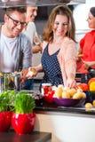 Amici che cucinano pasta e carne in cucina domestica Fotografia Stock