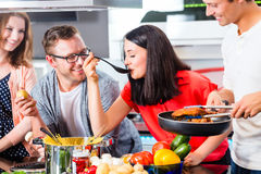 Amici che cucinano pasta e carne in cucina domestica Fotografie Stock