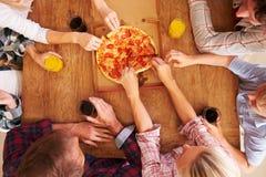 Amici che dividono insieme una pizza, vista sopraelevata fotografie stock