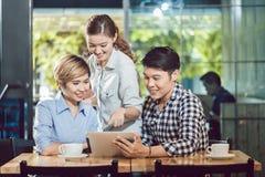 Amici che esaminano compressa digitale che si siede nella caffetteria immagine stock libera da diritti