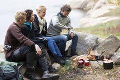 Amici che esaminano il caffè della macinazione dell'uomo il campeggio fotografia stock