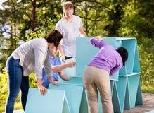 Amici che fanno piramide delle plance sul patio in foresta Fotografia Stock Libera da Diritti