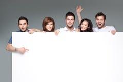 Amici che fanno pubblicità alla scheda bianca Fotografie Stock