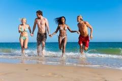 Amici che funzionano sulla vacanza della spiaggia immagine stock