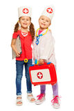 Amici che giocano al dottore con il corredo di pronto soccorso del giocattolo Immagine Stock