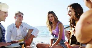Amici che giocano chitarra ed i tamburi sulla spiaggia 4k archivi video