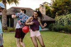 Amici che giocano i giochi schioccanti del pallone al partito fotografia stock