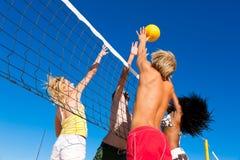 Amici che giocano pallavolo della spiaggia Immagini Stock