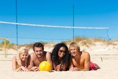 Amici che giocano pallavolo della spiaggia Fotografia Stock