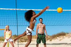 Amici che giocano pallavolo della spiaggia Immagine Stock