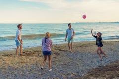 Amici che giocano pallavolo su una spiaggia selvaggia durante il tramonto Immagini Stock Libere da Diritti