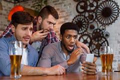 Amici che guardano calcio sullo smartphone nella barra fotografia stock libera da diritti