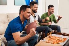 Amici che guardano football americano fotografie stock