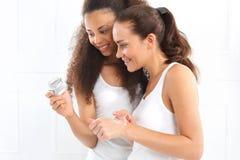 Amici che guardano i cosmetici, crema, lozione fotografie stock