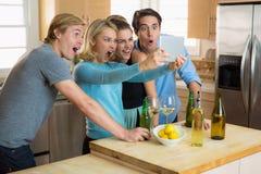 Amici che guardano i video su un dispositivo di Internet della compressa colpito al blog virale di risata sciocco divertente Fotografia Stock