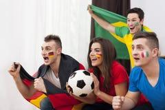 Amici che guardano partita di football americano sulla TV Fotografie Stock