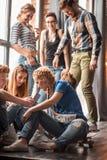 Amici che guardano Smart Phone mentre sedendosi in caffè La gente della corsa mista che si siede ad una tavola in ristorante face fotografie stock