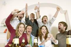 Amici che guardano televisione e che celebrano Immagine Stock