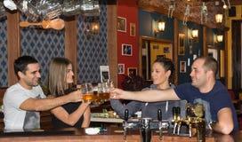 Amici che hanno bevande in una barra Immagine Stock Libera da Diritti