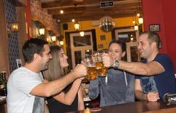 Amici che hanno bevande in una barra Fotografie Stock
