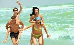 Amici che hanno divertimento alla spiaggia Fotografia Stock Libera da Diritti