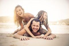Amici che hanno divertimento sulla spiaggia Fotografia Stock