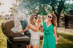 Amici che hanno un partito del barbecue, ragazze che ridono e che sorridono, beventi e cucinanti immagini stock libere da diritti