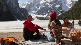 Amici che hanno un picnic sulla costa e che mangiano i panini intorno alle montagne stock footage