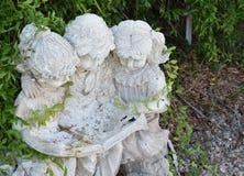Amici che leggono fuori della statua nell'iarda Fotografia Stock
