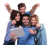 Amici che leggono su un computer del cuscinetto della compressa e sulle dita del punto Fotografia Stock Libera da Diritti