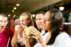 Amici che mangiano alimenti a rapida preparazione in un ristorante fotografia stock