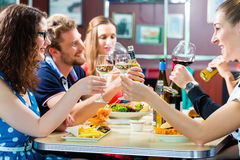Amici che mangiano e che bevono nella cena degli alimenti a rapida preparazione Immagine Stock