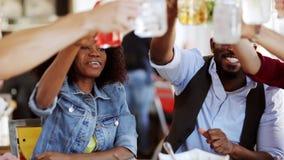 Amici che mangiano e vetri tintinnanti al ristorante stock footage