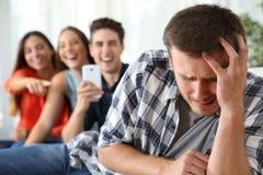 Amici che opprimono ad un ragazzo triste Fotografie Stock