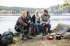 Amici che parlano sopra Lakeshore durante il campeggio fotografia stock