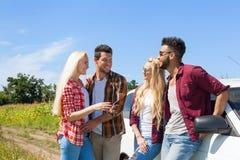 Amici che parlano sorriso all'aperto di chiacchierata della gente della campagna vicino all'automobile Immagini Stock