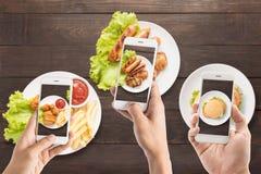 Amici che per mezzo degli smartphones per prendere le foto della salsiccia, braciola di maiale, Immagini Stock Libere da Diritti