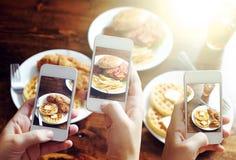 Amici che per mezzo degli smartphones per prendere le foto di alimento Fotografie Stock
