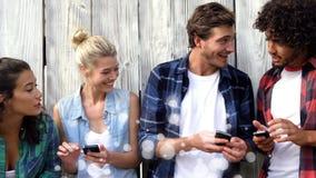 Amici che per mezzo dei loro telefoni cellulari circondati da effetto bianco delle bolle archivi video