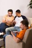 Amici che per mezzo del cellulare o degli Smart Phone a casa fotografie stock libere da diritti