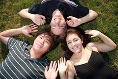 Amici che pongono sull'erba verde Fotografia Stock Libera da Diritti