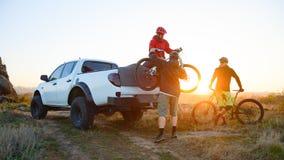 Amici che prendono le bici di MTB fuori dal camion fuori strada della raccolta in montagne al tramonto Concetto di viaggio e di a fotografia stock