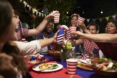 Amici che producono un pane tostato per celebrare il quarto della festa di luglio Fotografia Stock Libera da Diritti