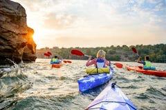 Amici che remano i kajak sul bello fiume o lago vicino all'alta roccia sotto il cielo drammatico di sera al tramonto Fotografia Stock